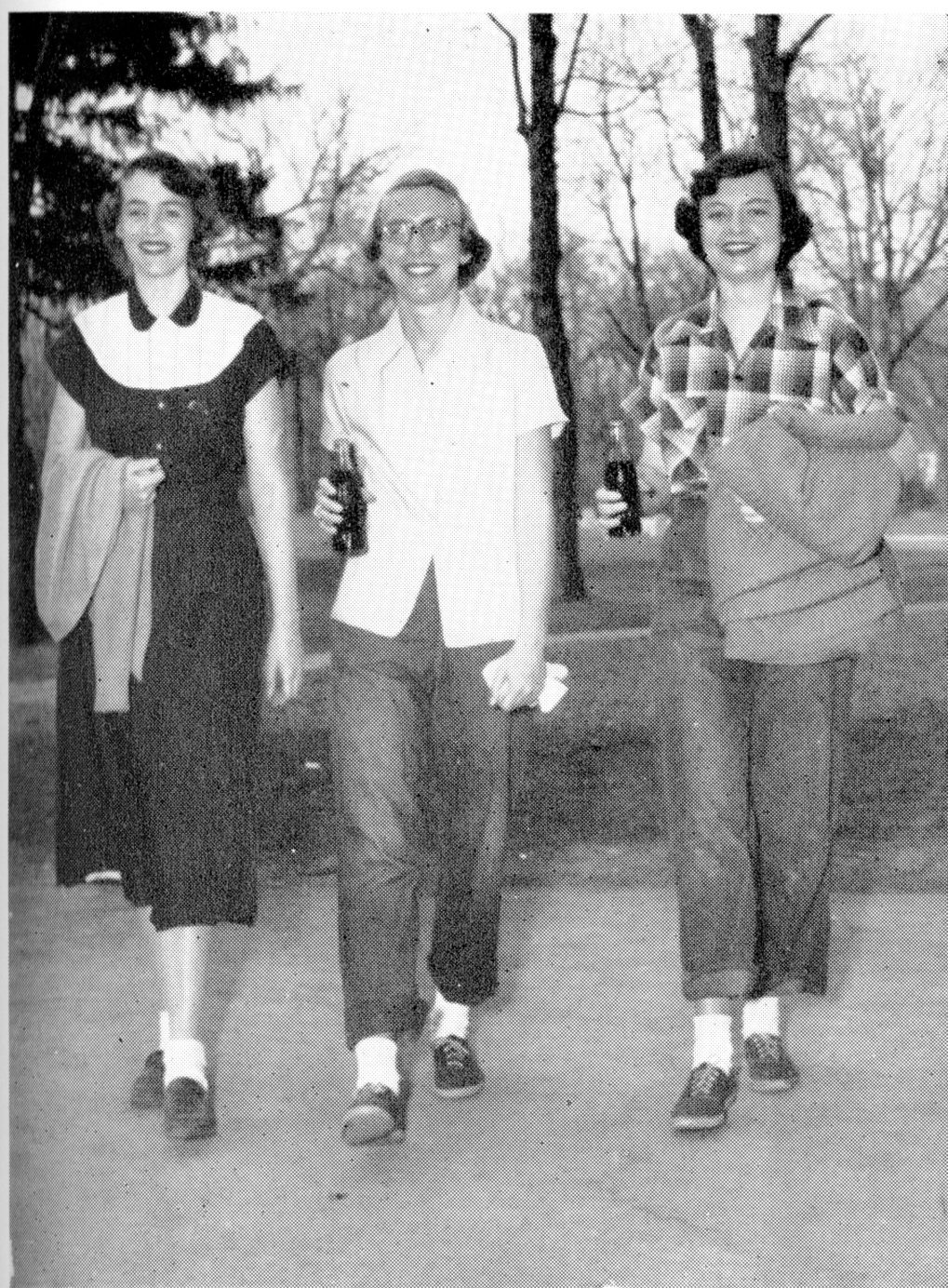 Three Girls Walking with Soda Bottles