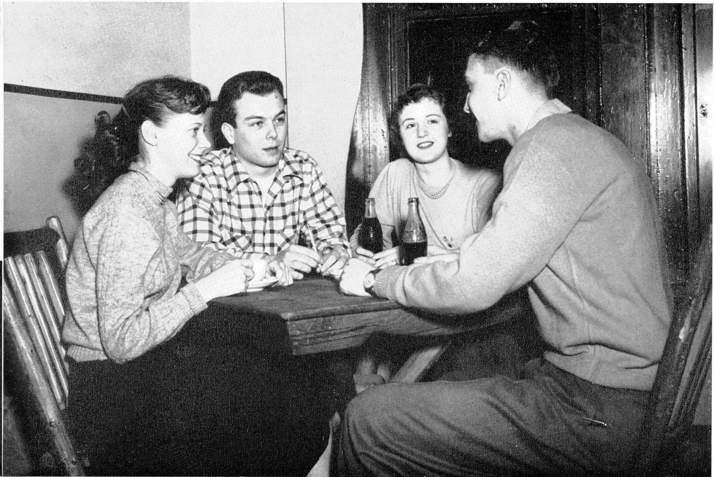 Group of Boys and Girls Sitting at Table with Coke Bottles