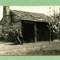 Two children (Barr and Clay Jr) sitting outside the Cabin