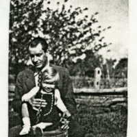 "Photocopy of a photogaph entitled ""occupants."" Present is an adult man holding a child [Pamela?] in front of him"