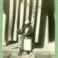 Frances Shaw and young grandchild [presumably Alice] standing in front of Ragdale presumable around the time of the Fourth of July (the large flag is present in the photograph)