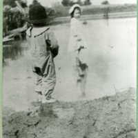 Two children playing at river's side