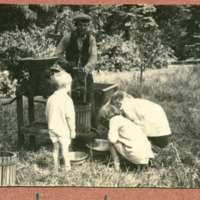 "Three children and one adult ""making cider"""