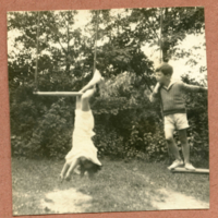 Two children playing on swings in the yard