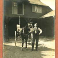 George (the coachman) next to horse in the barnyard