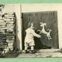 Alice standing by the berry patch gate (on gate a dog is painted, painted by John McCutcheon)