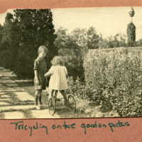 Two children, Jackie standing and Alice on a tricycle, along the path near the welláhead